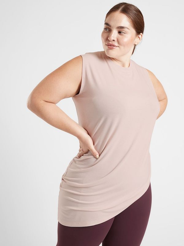 A plus-size model from Athleta wearing a light pink tank top.