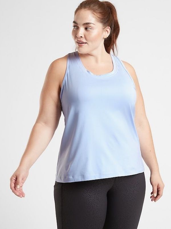 A plus-size model from Athleta wearing a light blue tank top.