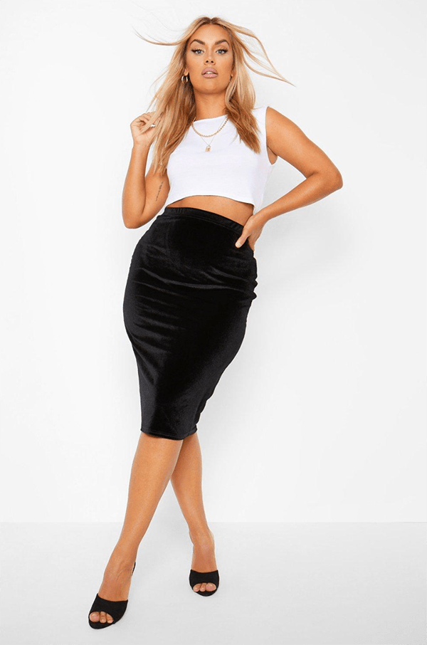 A plus-size model wearing a black velvet pencil skirt, which will be on sale at Boohoo's 2020 Black Friday sale.