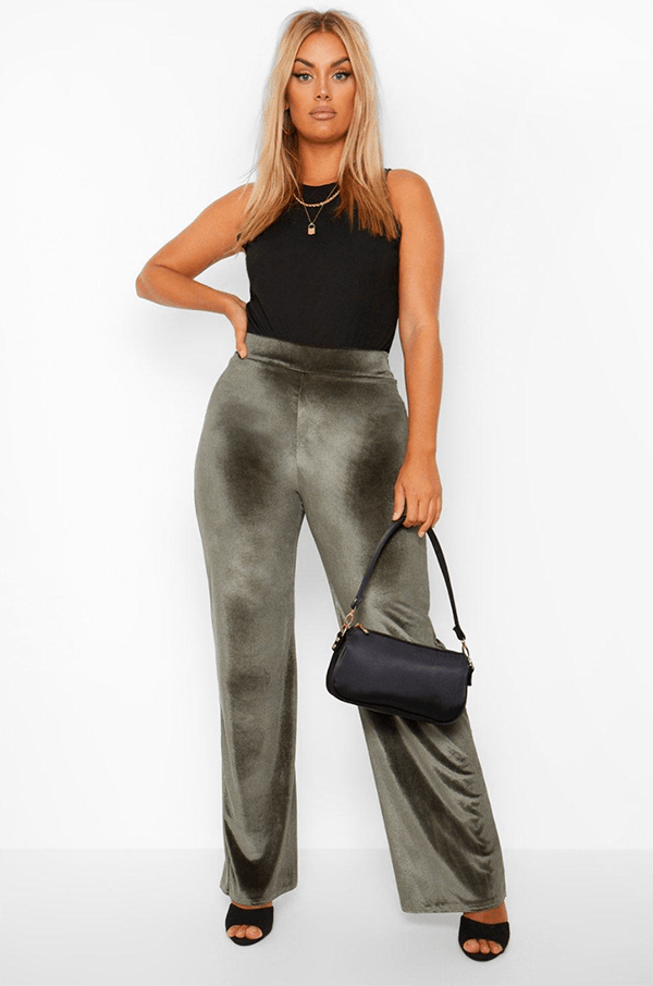 A plus-size model wearing velvet pants, which will be on sale at Boohoo's 2020 Black Friday sale.