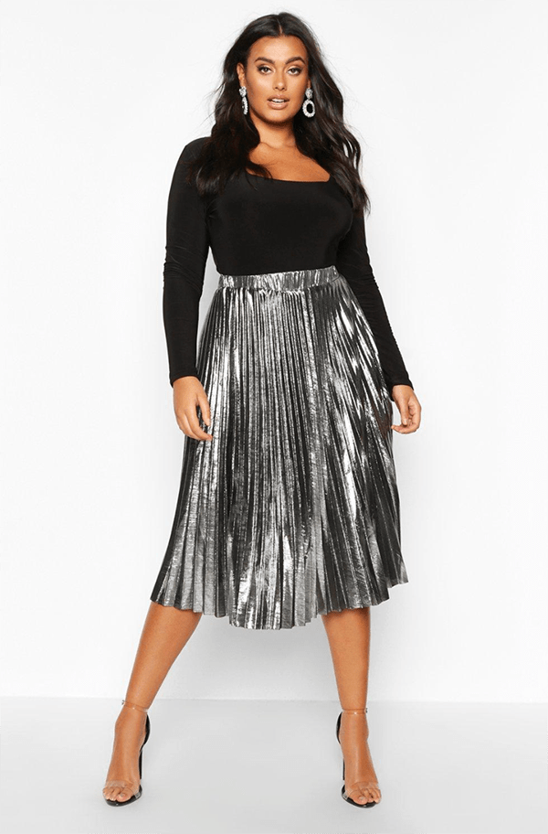 A plus-size model wearing a silver pleated skirt, which will be on sale at Boohoo's 2020 Black Friday sale.