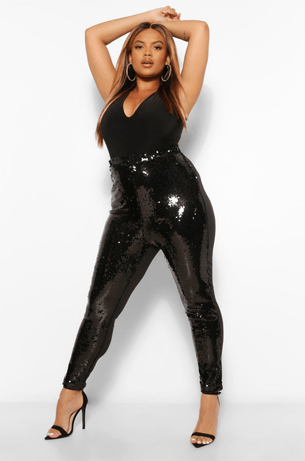 A plus-size model wearing black sequin leggings, which will be on sale at Boohoo's 2020 Black Friday sale.