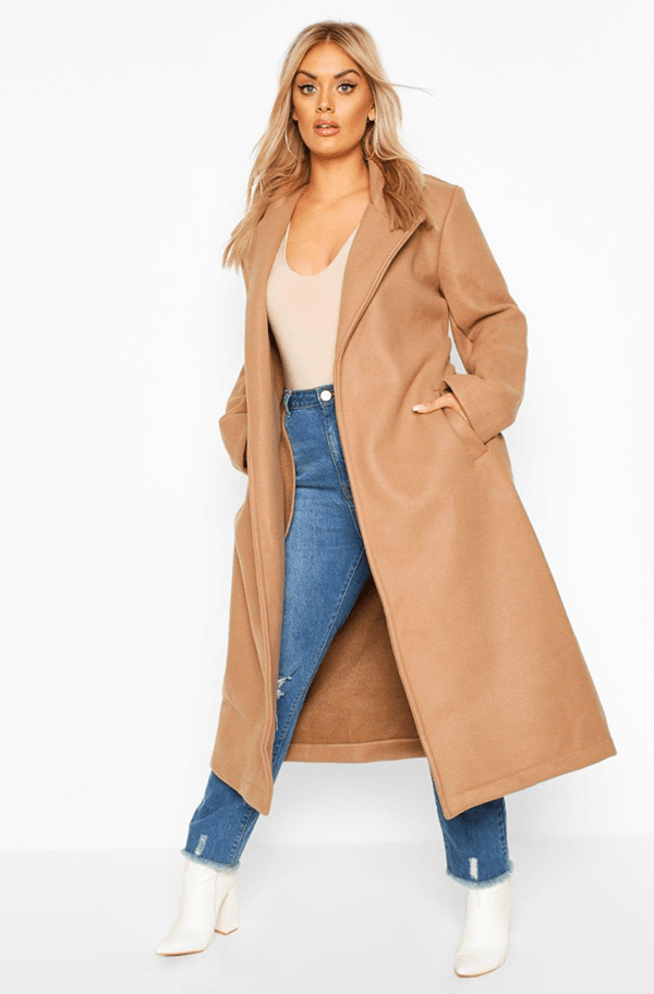 A plus-size model wearing a tan trench coat, which will be on sale at Boohoo's 2020 Black Friday sale.