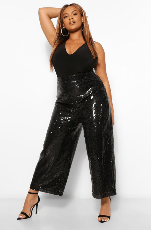 A plus-size model wearing black sequin pants, which will be on sale at Boohoo's 2020 Black Friday sale.