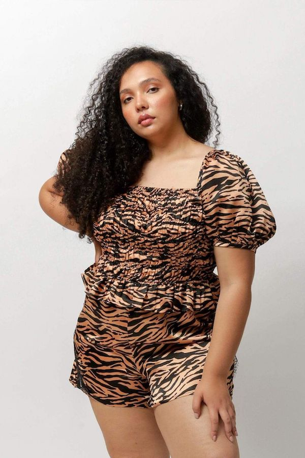 A plus-size model from CoEdition's Black Friday sale wearing an animal print top and shorts.