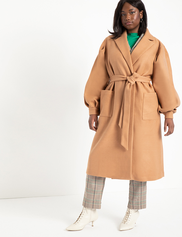A plus-size model wearing a camel trench coat, which will be marked down at Eloquii's 2020 Black Friday sale.