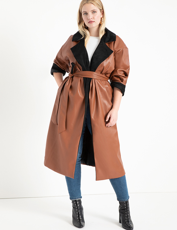 A plus-size model wearing a brown leather trench coat, which will be marked down at Eloquii's 2020 Black Friday sale.