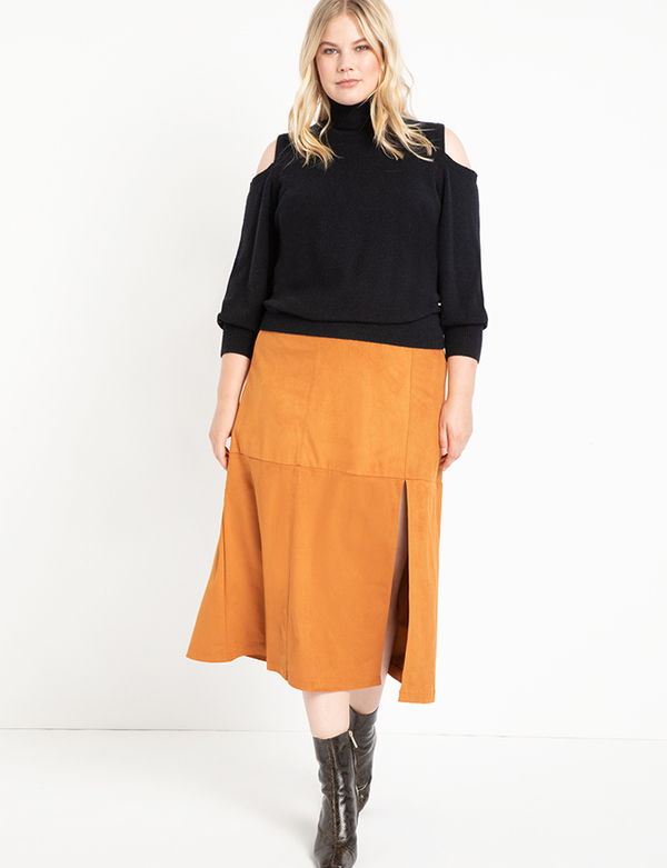 A plus-size model wearing a brown suede midi skirt, which will be marked down at Eloquii's 2020 Black Friday sale.