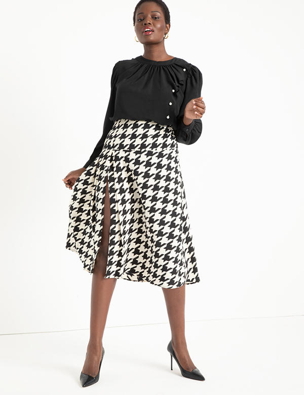 A plus-size model wearing a houndstooth midi skirt, which will be marked down at Eloquii's 2020 Black Friday sale.