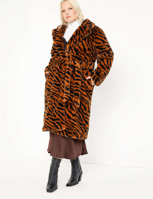 A plus-size model wearing a faux fur coat, which will be marked down at Eloquii's 2020 Black Friday sale.