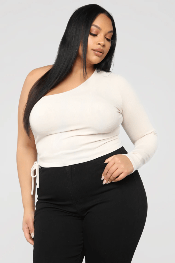 A plus-size model from Fashion Nova wearing a one-shoulder cream top.