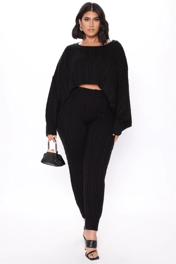 A plus-size model from Fashion Nova wearing a black sweater set.