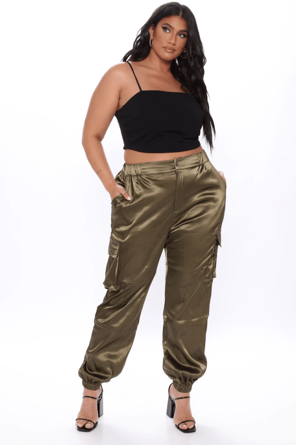 A plus-size model from Fashion Nova wearing olive satin pants.