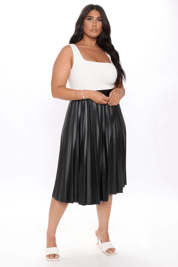 A plus-size model from Fashion Nova wearing a black pleated skirt.