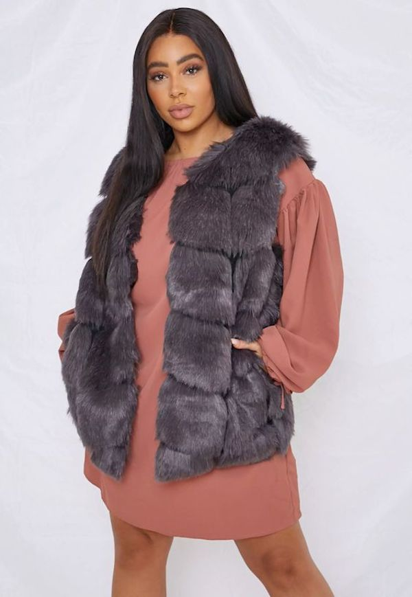 A plus-size model wearing a gray faux fur vest from Missguided.