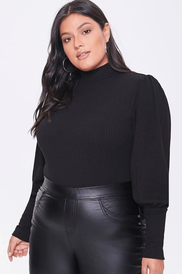A plus-size model wearing a black turtleneck.