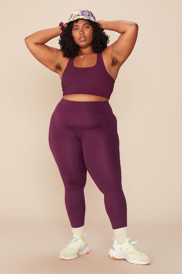 A plus-size model from Girlfriend wearing plum colored leggings