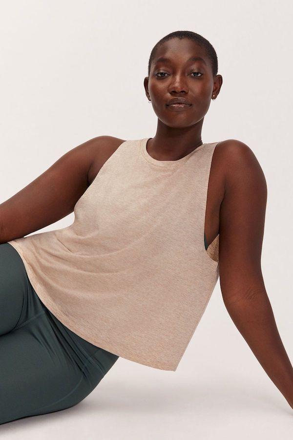 A plus-size model from Girlfriend wearing a tan tank top.