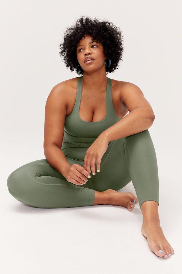 A plus-size model from Girlfriend wearing green leggings.