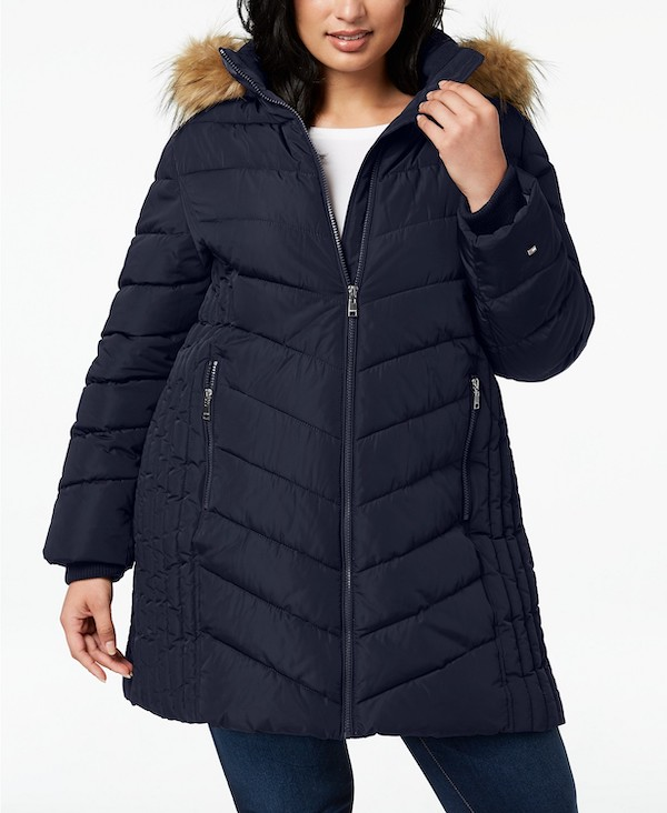 A plus-size model from Macy's wearing a navy puffer coat with a faux fur hood.