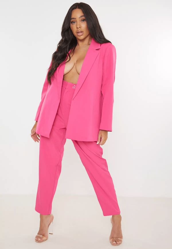 A plus-size model for Missguided wearing a hot pink suit.