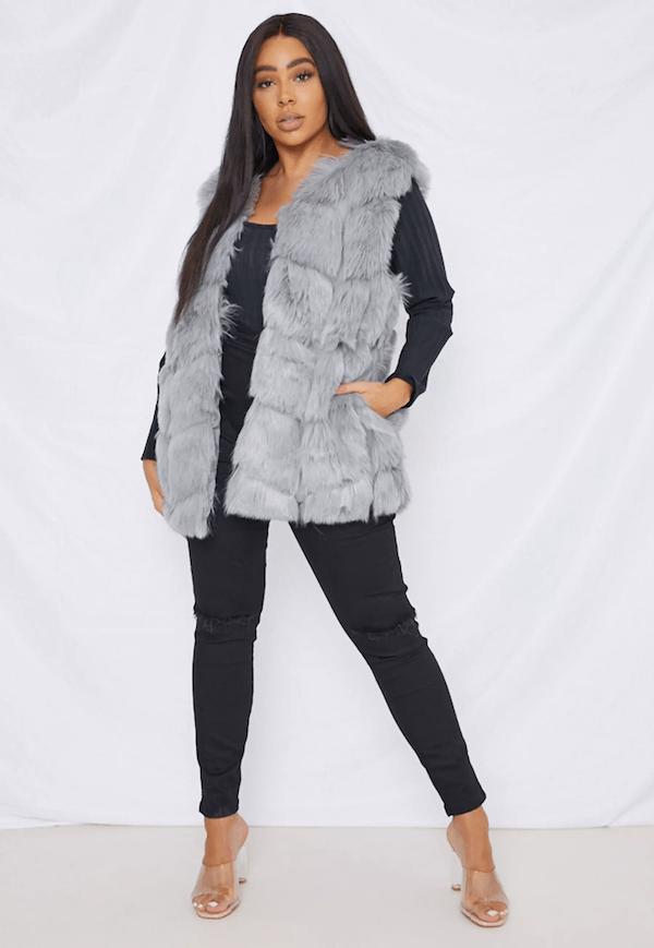 A plus-size model for Missguided wearing a faux fur vest.