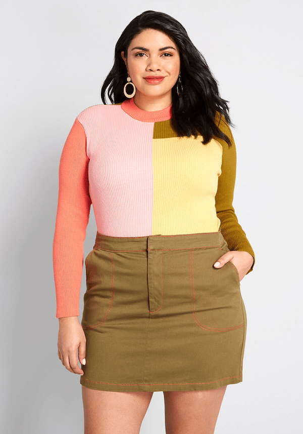 A plus-size model from ModCloth wearing a color block sweater.