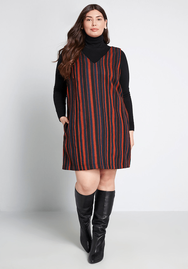 A plus-size model from ModCloth wearing a red and blue jumper dress.
