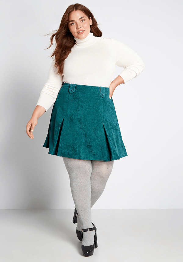 A plus-size model from ModCloth wearing a turquoise mini skirt.