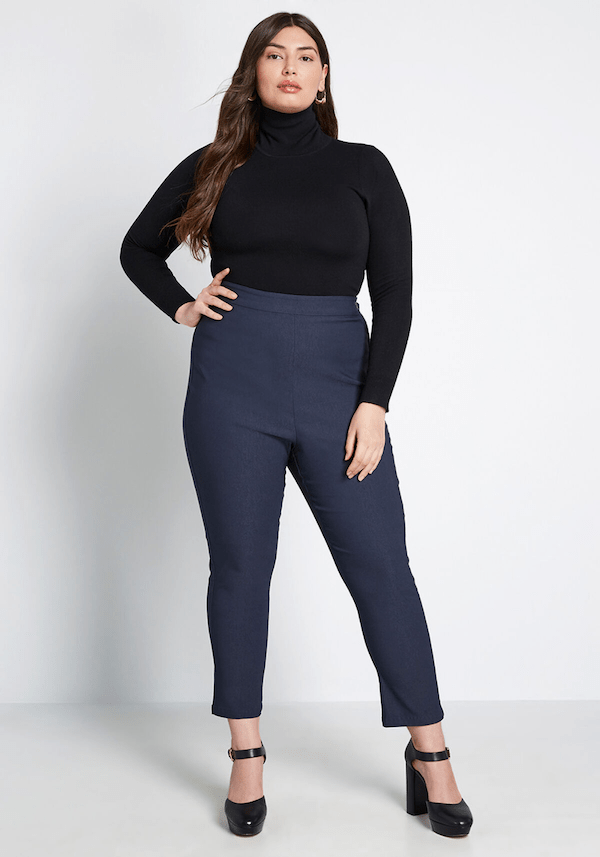 A plus-size model from ModCloth wearing navy trousers.