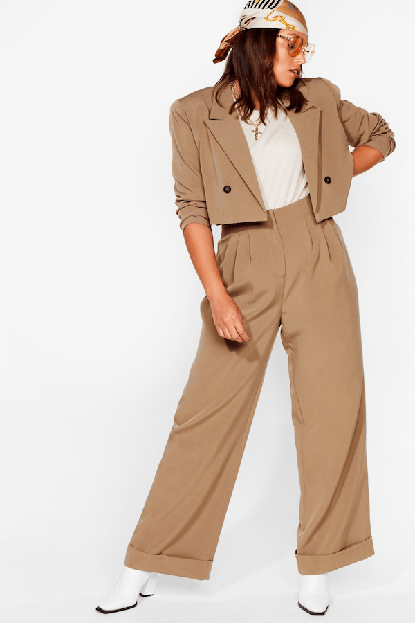 A plus-size model from Nasty Gal wearing a brown suit.