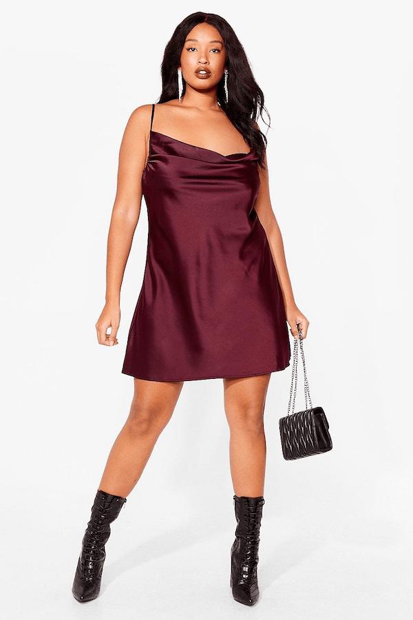 A plus-size model from Nasty Gal wearing a dark red slip mini dress.