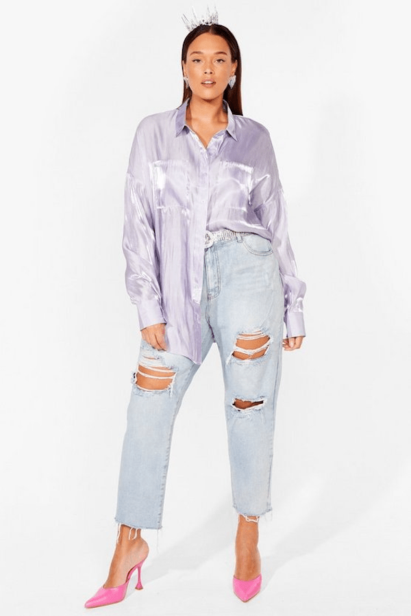 A plus-size model from Nasty Gal wearing a lavender button up blouse.