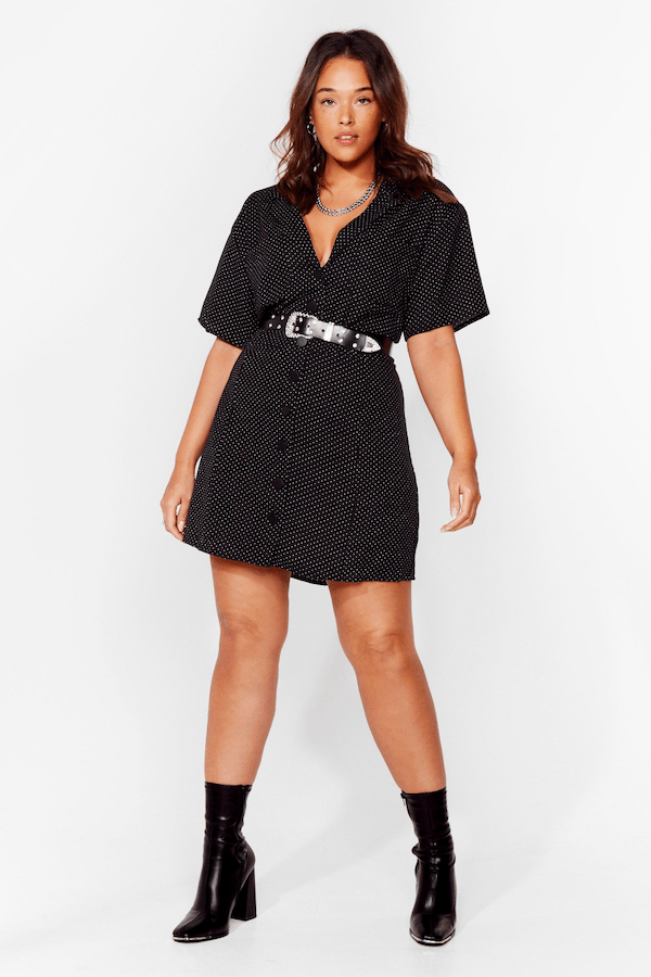 A plus-size model from Nasty Gal wearing a belted black mini dress.