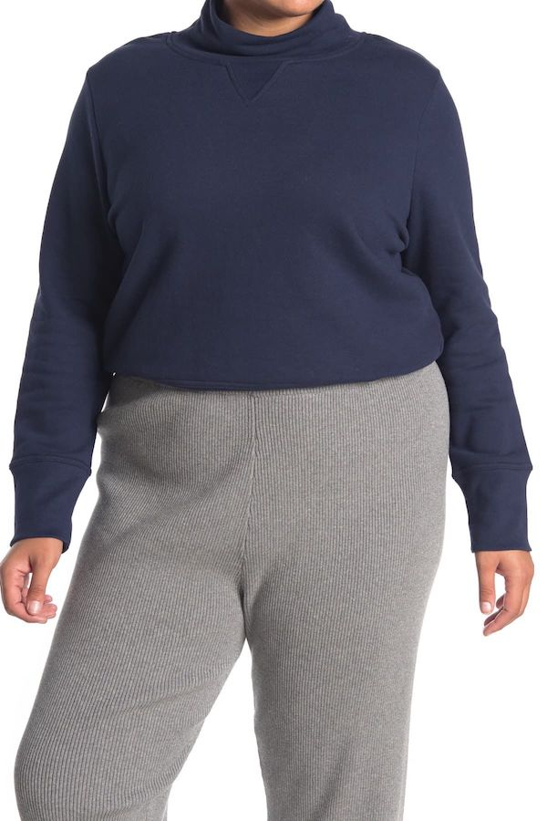 A plus-size model from Nordstrom Rack wearing a navy blue sweater.