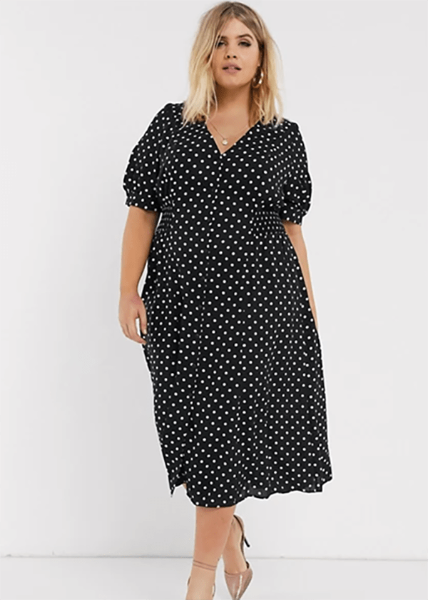 A plus-size model wearing a black polka dot dress, which is currently marked down at ASOS's 2020 Black Friday sale.