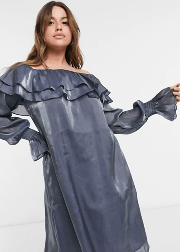 A plus-size model wearing a blue off-the-shoulder dress, which is currently marked down at ASOS's 2020 Black Friday sale.