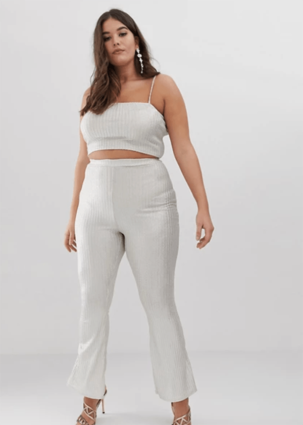 A plus-size model wearing a white glittery matching set, which is currently marked down at ASOS's 2020 Black Friday sale.