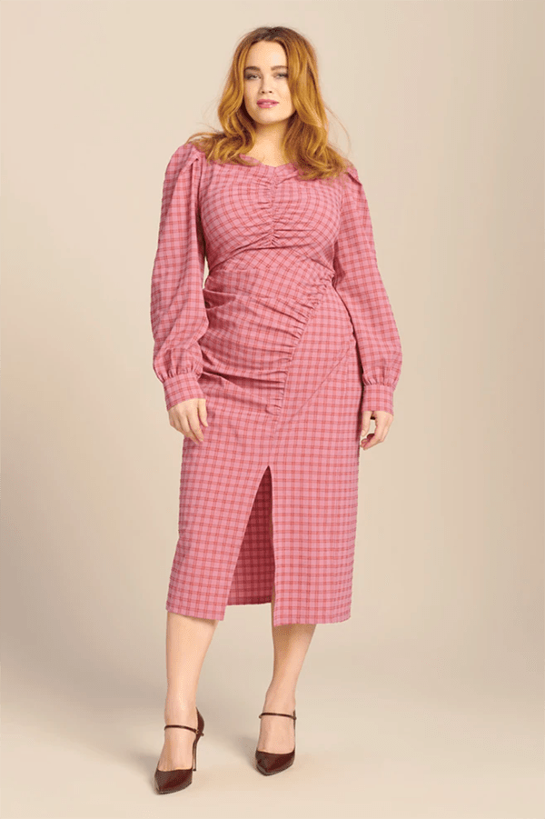 A plus-size model wearing a pink plaid dress, which is currently marked down at 11 Honore's 2020 Black Friday sale.