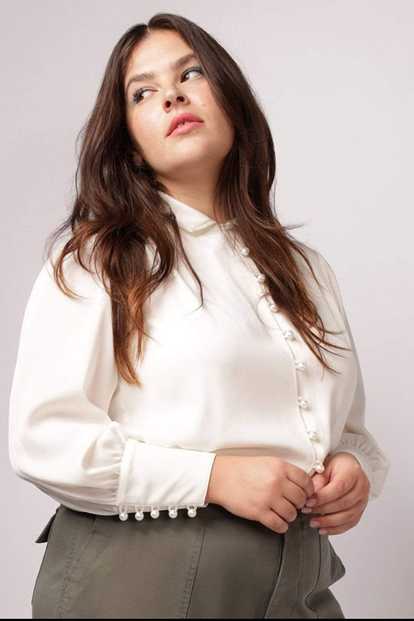 A plus-size model wearing a white button-down shirt, which is currently marked down at CoEdition's 2020 Black Friday sale.