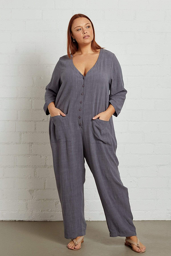 A plus-size model wearing a gray jumpsuit, which is currently marked down at CoEdition's 2020 Black Friday sale.