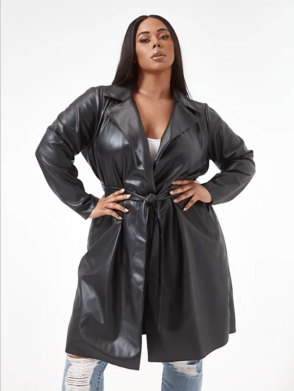 A plus-size model wearing a black leather trench coat, which will be marked down at Fashion to Figure's 2020 Black Friday sale.