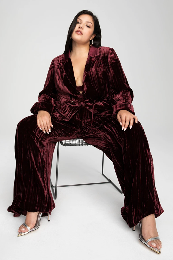 A plus-size model wearing red velvet pants, which will be marked down at Good American's 2020 Black Friday sale.
