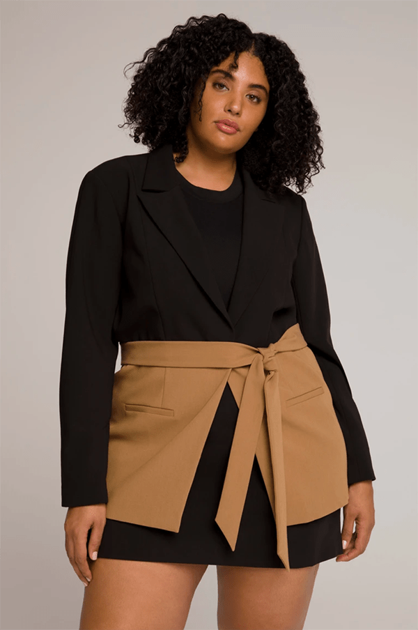 A plus-size model wearing a black and brown wrap blazer, which will be marked down at Good American's 2020 Black Friday sale.