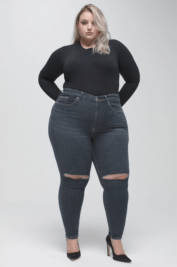 A plus-size model wearing black distressed skinny jeans, which will be marked down at Good American's 2020 Black Friday sale.