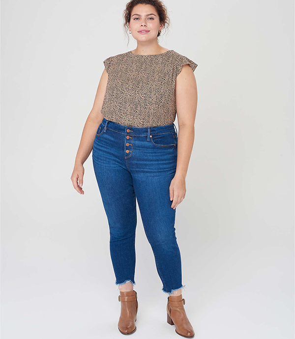 A plus-size model wearing a pair of skinny jeans, which will be marked down at Loft's 2020 Black Friday sale.