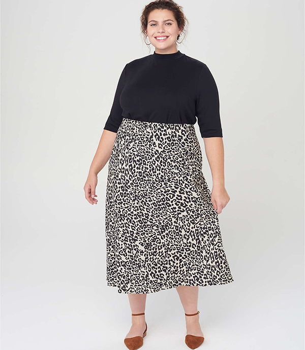 A plus-size model wearing an animal print midi skirt, which will be marked down at Loft's 2020 Black Friday sale.