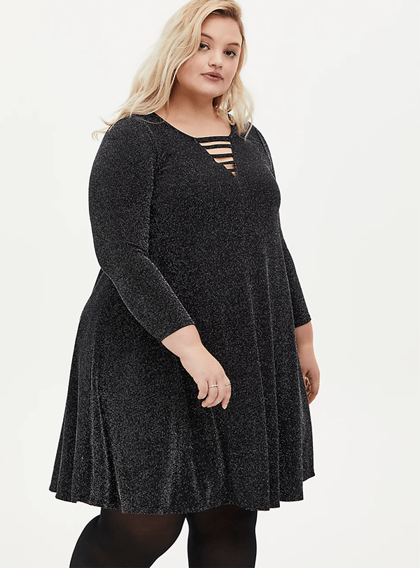 A plus-size model wearing a glittery black dress, which will be marked down at Torrid's 2020 Black Friday sale.