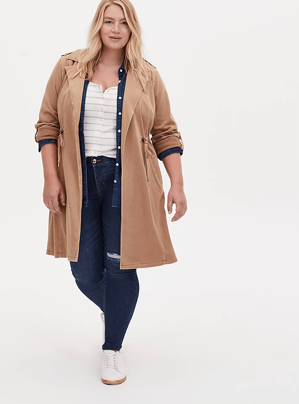 A plus-size model wearing a camel trench coat, which will be marked down at Torrid's 2020 Black Friday sale.
