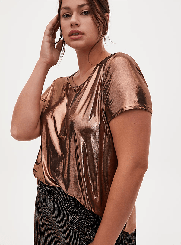 A plus-size model wearing a metallic gold shirt, which will be marked down at Torrid's 2020 Black Friday sale.